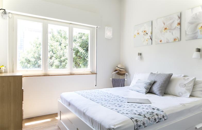 חדר השינה הראשי בבית, שומר על סקאלת הגוונים הבהירה והאוורירית.
