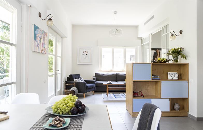 המיקום שנבחר לחלל הציבורי מפיק את המיטב מהכיוונים של הדירה ומהחלונות הענקיים. הספה והכורסא בסלון מבית אייטמס. כוננית המדפים מכילה, בצידה השני, את הטלוויזיה.