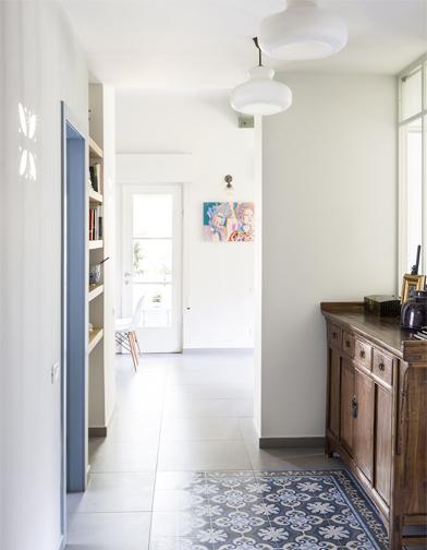מבט מדלת הכניסה לבית. מימין שידה עתיקה שבעלת הבית הביאה מסין לפני שנים. שטיח מצויר בהדפסה של סטודיו ורדי במרכז המבואה.  ציור של ניני מגלריה מיקה נתלה על הקיר המרכזי.