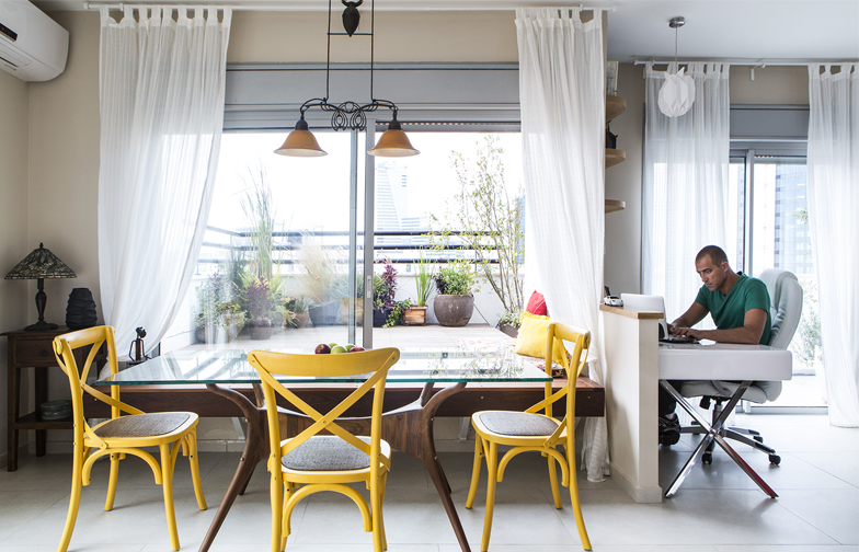 שולחן העבודה מוקם כנגד קיר נמוך בחלק מואר ופתוח של הסלון, מול הנוף. מעבר לחצי הקיר מוקמה פינת אוכל משוק הפשפשים.