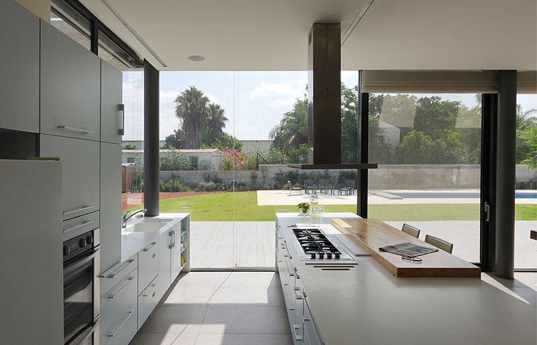 צילום: עוזי פורת - המטבח בשני פסים מקבילים בוצע על ידי חברת רגבה. משטחי העבודה עשויים קוריאן לבן , ומשטח האכילה מבוצ'ר אלון.