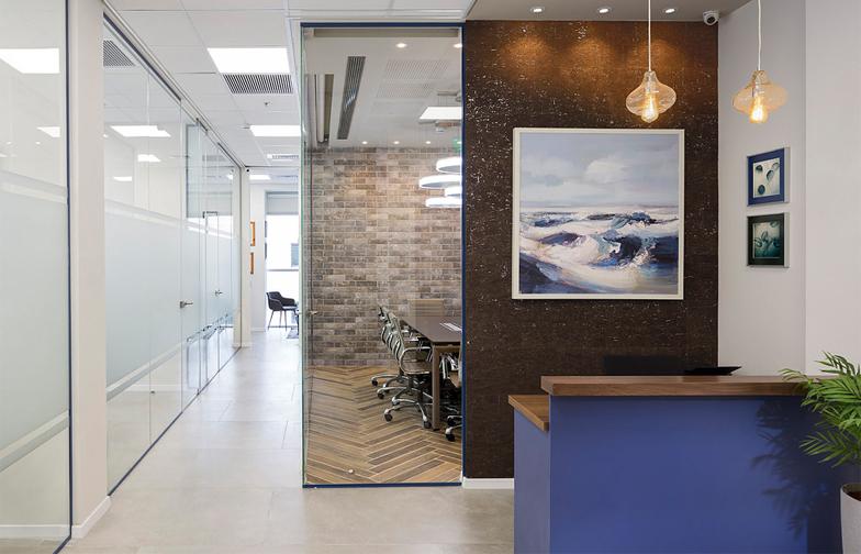 בכניסה למשרד, עמדת קבלה בכחול עמוק ועץ אגוז, קיר דקורטיבי וציור שמן מקבלים את פני הבאים. כבר מהכניסה ניתן לראות את חדר הישיבות ואת המסדרון המוביל למשרדים השונים.