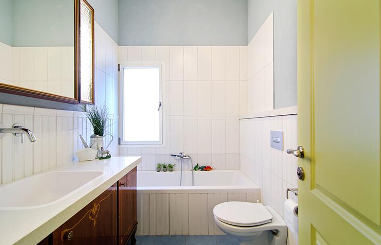 צילום: אילן נחום - בחדר הרחצה הכללי, רצפה כחולה, אריחים לבנים שמדמים פאנלים מעץ ושליכט אקרילי תכול על הקירות.