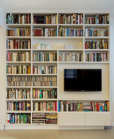 בתים שיש בהם הרבה ספרים דורשים התייחסות מיוחדת. חשוב לי להציג אותם באופן נעים ונגיש. בקיר זה גם מדפי דיסקים, מגירה עם דיוידי של הילדים ואלבומי משפחה. (צילום: אוה גז)