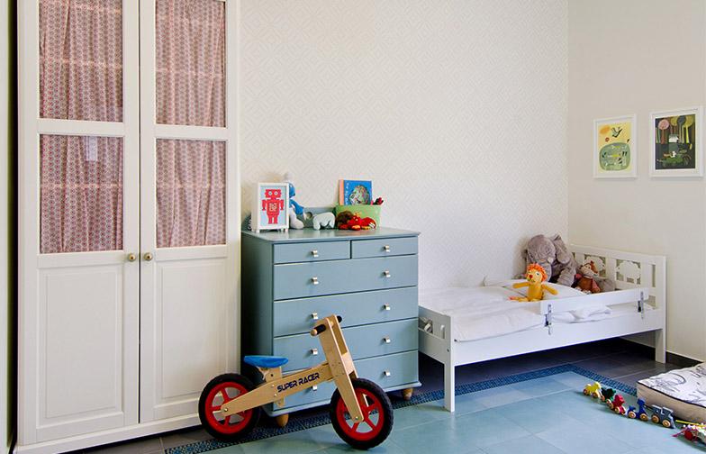 צילום: אילן נחום - חדר הילדים רוצף גם הוא בשטיח מודפס, בדוגמא עדינה יותר. על הקיר טפט, וספריה של איקאה הפכה לארון בגדים.