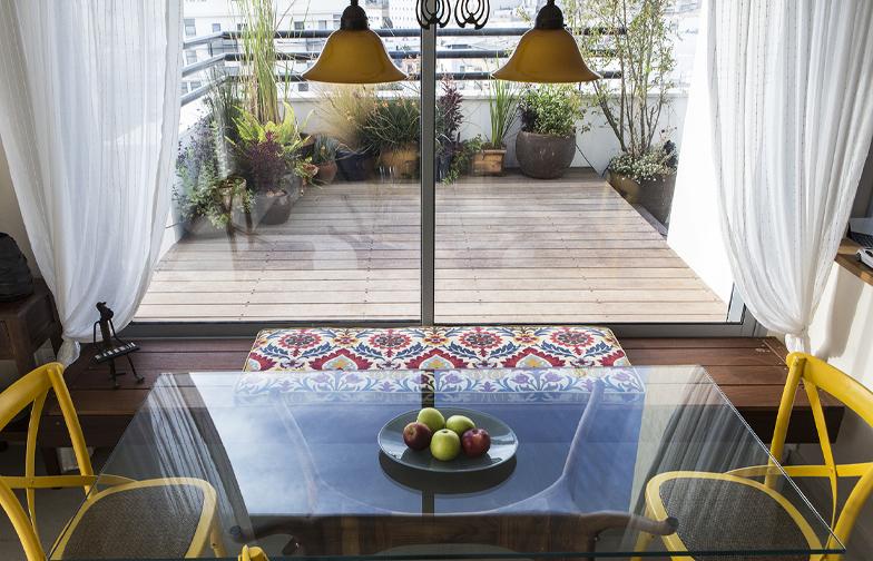 צילום: איתי בנית - מבט על הדק במרפסת, שגולש אל תוך הבית והופך לספסל בפינת האוכל, וכך מחבר בין הפנים והחוץ.
