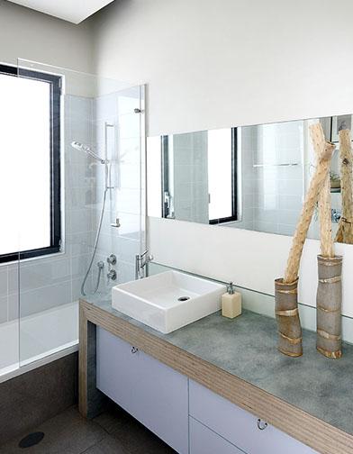 צילום: עוזי פורת - שירותי אורחים עם כיור מונח, משטח המורכב משכבות של סנדוויץ', וסל כביסה מתחת לכיור.