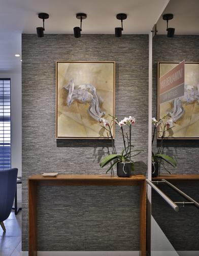 צילום: שי אפשטיין - הכניסה למשרד. קונסולה דקה מבמבוק, (עבודה של אלינור בלומברג) קיר מחופה טפט ועבודת אמנות.