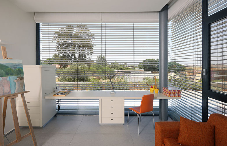 צילום: עוזי פורת - חדר העבודה והאירוח מכיל שתי עמדות עבודה וספה נפתחת לאורחים. לבית שתי מערכות הצללה - מערכת תריסים חיצונית ומערכת וילונות רומיים פנימית.