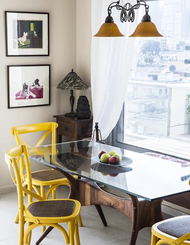 את פינת האוכל מקיפים כסאות עץ בשילוב ראטן בצבע צהוב.  על הקיר תמונות שיצרה אמו של בעל הבית .