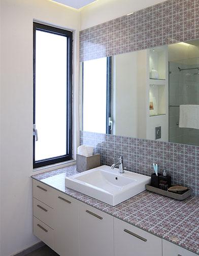צילום: עוזי פורת - חדר הרחצה של בעלי הבית. משטח הכיור וחיפוי הקיר עשויים זכוכית מודפסת, כשבתוכה משובצת מראה.