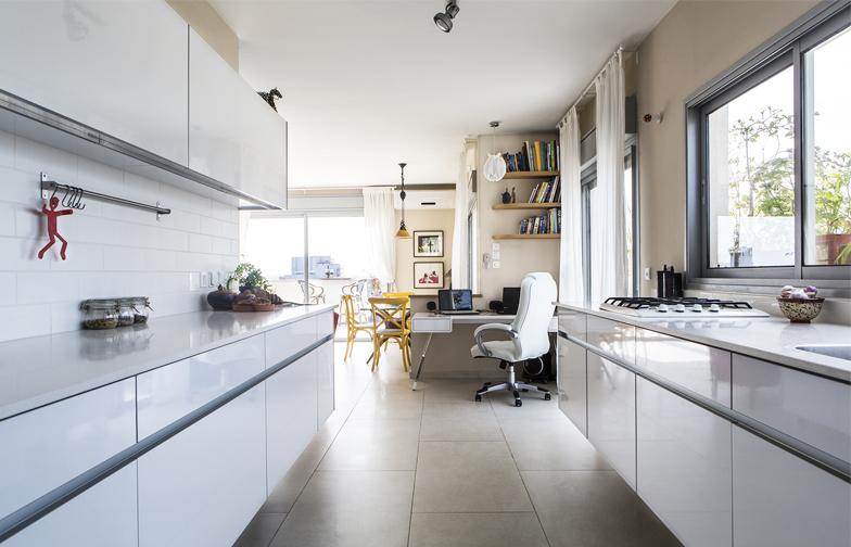 בין הסלון לחדרי השינה מפריד מסדרון רחב, שנוצל לטובת מטבח מוארך – שני קווים מקבילים של ארונות לבנים בגימור מבריק.