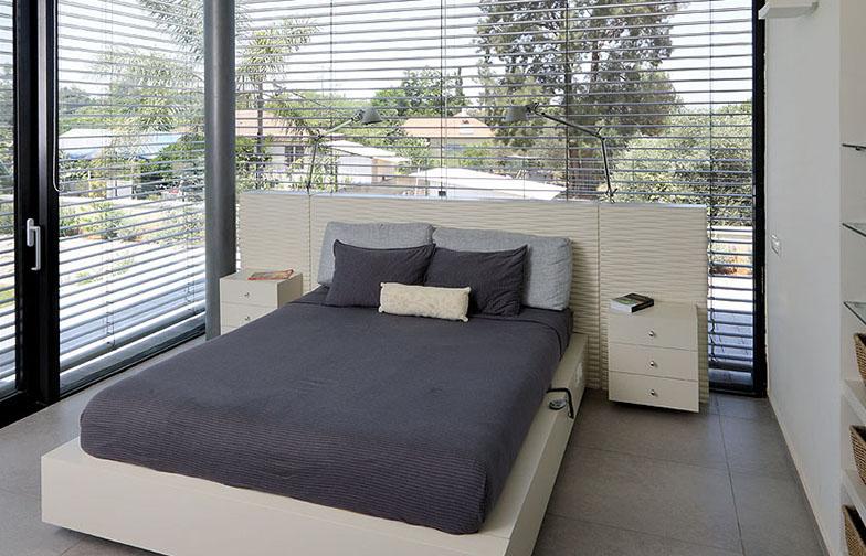 צילום: עוזי פורת - חדר השינה גם הוא בעל שני קירות זכוכית. המיטה תוכננה במיוחד ובתוכה מותקנים המפסקים לתאורה, החשמל למיטה המתכווננת, חוטי הטלפון ועוד.