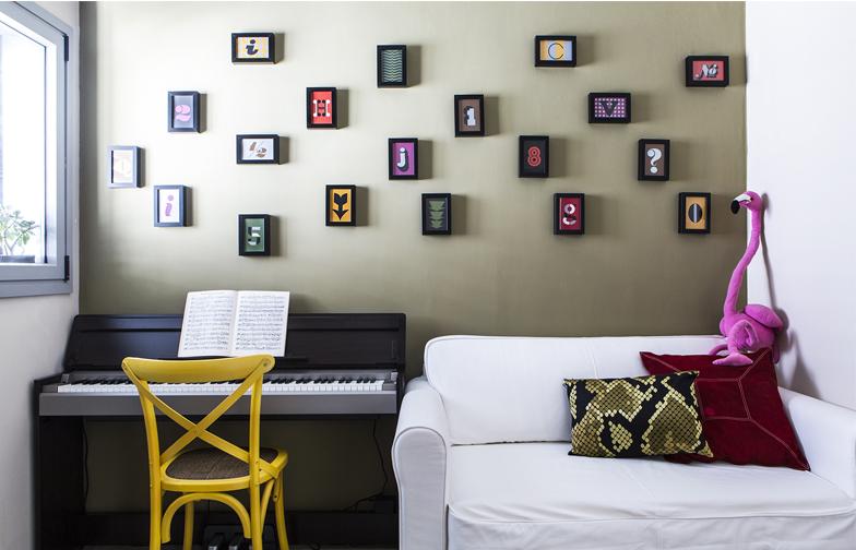 """חדר אורחים. אחד מקירותיו נצבע בירוק-זית ועליו נתלו גלויות שהוזמנו ברשת (סטודיו """"House industry"""") ומוסגרו."""