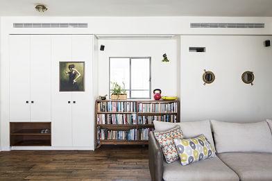 הרהיט הלבן בכניסה לביתם של ליאת וטל הוא רהיט כניסה לכל דבר. התוכו נמצאים האופניים המתקפלים של טל, קסדות הילדים, מעילים ותיקים. במדיפים הפתוחים מניחים נעליים (נגרות: נדב שליט. צילום: איתי בנית)