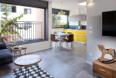 הסלון פתוח אל המטבח ליצירת חלל ציבורי משותף ומרווח. על הקיר  טפט מעוינים אפור, ועליו תלויה הטלוויזיה.