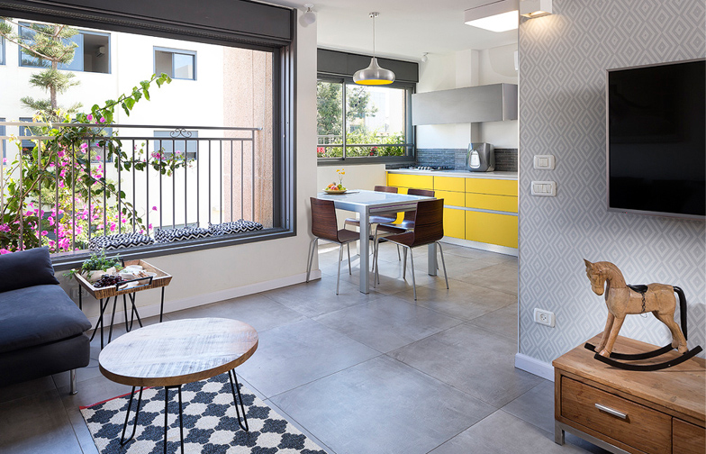 צילום: שי אפשטיין - הסלון פתוח אל המטבח ליצירת חלל ציבורי משותף ומרווח. על הקיר  טפט מעוינים אפור, ועליו תלויה הטלוויזיה.