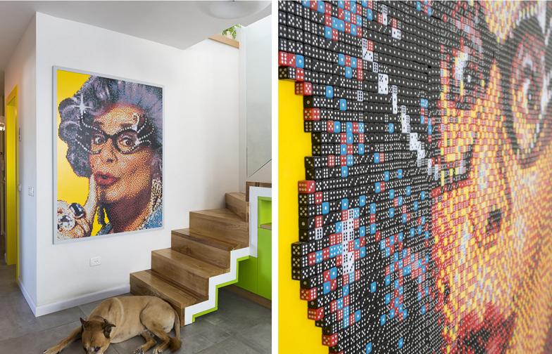 """צילום: שי אפשטיין - לצד המדרגות נתלתה תמונה של האמן <a href=""""http://eyalbtvs.wix.com/eyalophir""""  target=""""_blank"""">איל אופיר</a>  בדמותה של דיים עדנה המיתולוגית. העבודה עשויה מ 25,000 קוביות משחק בארבעה צבעים, והוכנה לפי הזמנה לחלל."""