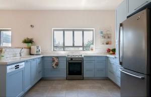 המטבח הוא בצורה של ח', עם דלתות מילואה צבועות בשלייפלק בגוון תכלת (רגבה).