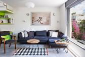 בסלון הבית ספה אפורה, גוונים מונכרומטיים שמאזנים את הצבעוניות מסביב, ושולחנות ברזל ועץ. תמונה של הצלם מוטי שושן תלויה מעל הספה.