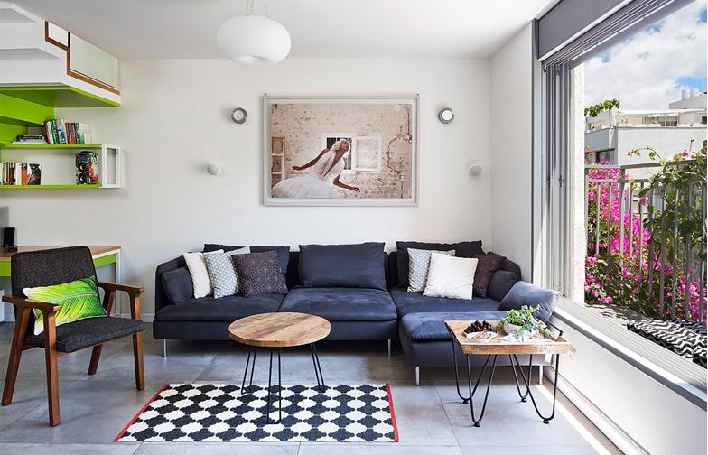 צילום: שי אפשטיין - בסלון הבית ספה אפורה, גוונים מונכרומטיים שמאזנים את הצבעוניות מסביב, ושולחנות ברזל ועץ. תמונה של הצלם מוטי שושן תלויה מעל הספה.