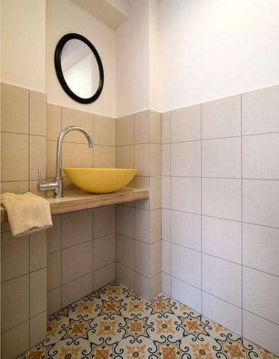 צילום: אילן נחום - שירותי אורחים: רצפת גרניט פורצלן מצויירת וכיור מונח מקוריאן צהוב.