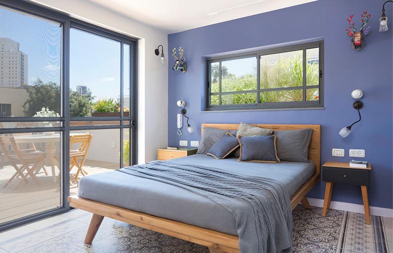 """צילום: שי אפשטיין - בקומה השניה, אשר גודלה 19 מ""""ר, נמצאת סוויטת הורים. חדר השינה של בני הזוג פתוח אל מרפסת הגג, ונהנה מהאור והצמחיה בו. שטיח ריצוף מצויר תוחם את המיטה,. הצבעוניות עדיין נוכחת אך כאן היא מעושנת ומרוככת יותר."""