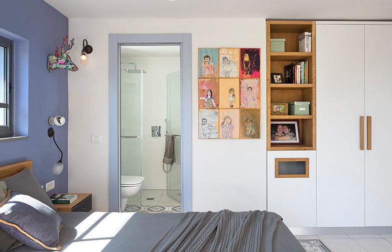 צילום: שי אפשטיין - בחדר השינה תוכננו פתרונות איחסון פונקציונלים, הכוללים ארון פינתי, מדפי ספרים וסל כביסה. דלת הכניסה לחדר הרחצה היא דלת הזזה לתוך כיס, כדי לחסוך במקום..