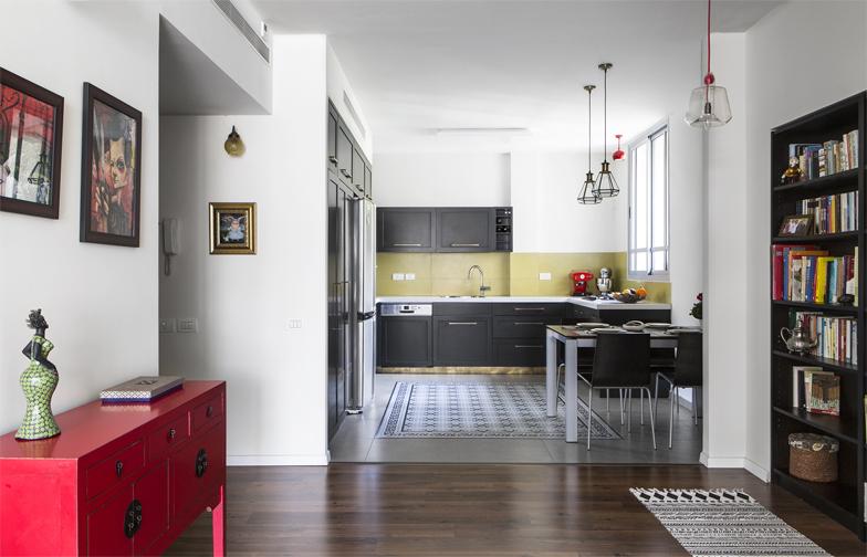צילום: איתי בנית - המטבח נמצא מצידה השני של הכניסה, ורוצף באריחים אפורים חלקים ומצויירים.