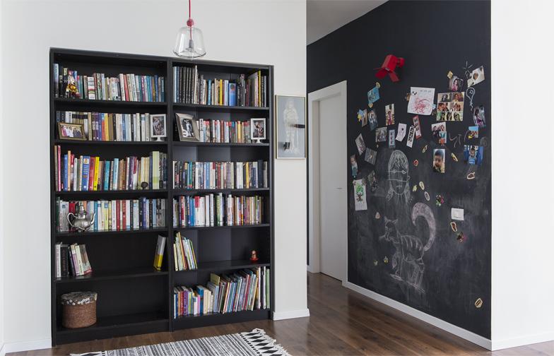 צילום: איתי בנית - מול הדלת, ספריה בתוך נישה, ולצידה, קיר לוח-מגנט שמוביל אל החללים הפרטיים של הבית. גם ההורים וגם הילדות עושים שימוש רב בקיר: מציירים, משאירים הודעות, תולים תמונות ויצירות. הוא מהווה 'לב הבית' ביותר ממובן אחד.