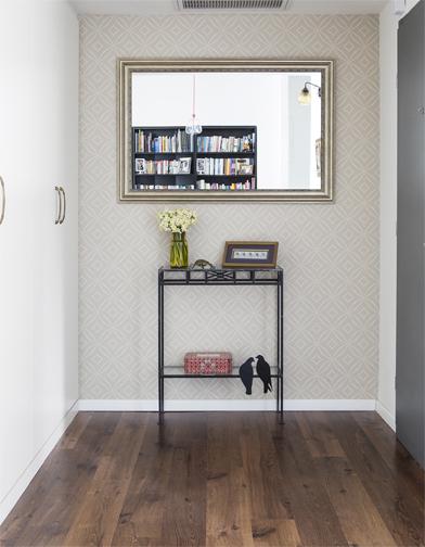 """צילום: איתי בנית - מבט אל המבואה: טפט ומראה מצד אחר, וארון של 2 מטר מצד שני. כשנכנסים הביתה """"פורקים"""" הכל: מעילים, נעליים, תיקים, מטריות - ומאפסנים לארון שתוכנן בהתאם. הבית נשאר מסודר ונעים ככה."""